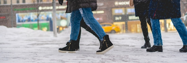 Le gambe della gente con gli stivali camminano in una giornata nevosa. concetto di moda nella strada della città f