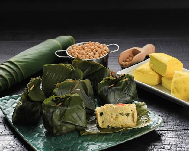 Pepes tahu è il tofu speziato indonesiano avvolto con foglie di banana e cotto a vapore, cibo tipicamente indonesiano di giava occidentale (sudanese). tofu al vapore con basilico asiatico. servito su piatto intrecciato, sfondo nero