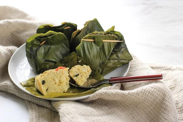 Pepes tahu è il tofu speziato indonesiano avvolto con foglie di banana e cotto a vapore, cibo tipicamente indonesiano di giava occidentale (sudanese). tofu al vapore con basilico asiatico, sfondo bianco