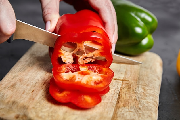 Affettare il pepe. mani, coltello e peperoni rossi, verdi, gialli, tagliere di legno sul tavolo di pietra. peperoni dolci a fette su sfondo nero. ingrediente vegetale, cucina insalata dietetica, cibo sano