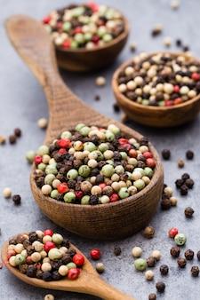 Mix di grani di pepe in una ciotola di legno sul tavolo grigio.