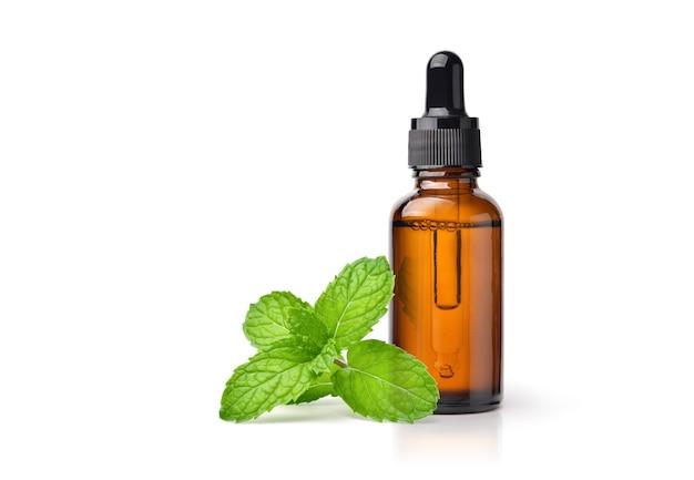 Olio essenziale di menta piperita in flacone contagocce ambra con foglia di menta fresca isolato su sfondo bianco.