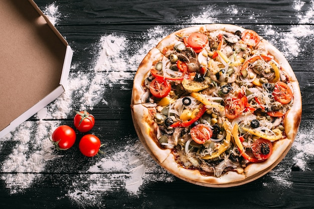 Pizza ai peperoni accanto a una scatola per il confezionamento di farina versata su un tavolo di legno nero