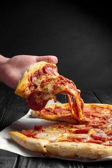 Pizza ai peperoni sul bordo di legno nero scuro, pezzo di pizza in mano, pizza italiana tradizionale