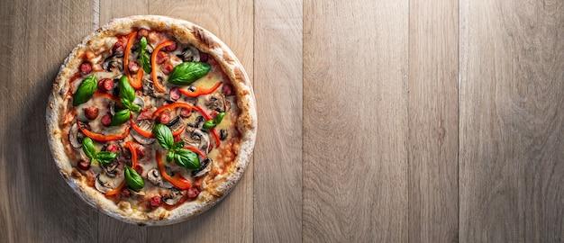 Pizza ai peperoni con salsiccia dei cacciatori funghi peperoni rossi e basilico fresco su un tavolo di legno