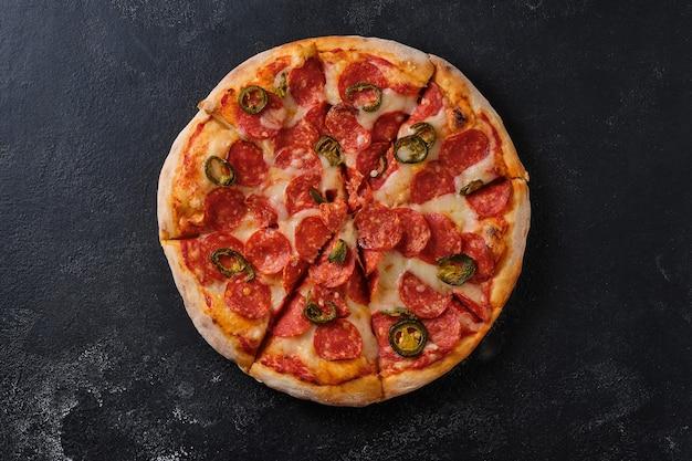 Pizza ai peperoni con peperoni jalapeno un primo piano di una pizza piatto adagiato su uno sfondo scuro