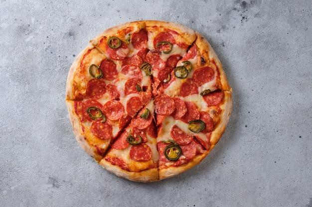 Pizza ai peperoni con peperoni jalapeno un primo piano di una pizza piatto lay