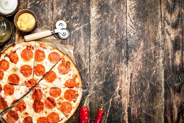Pizza ai peperoni con salse