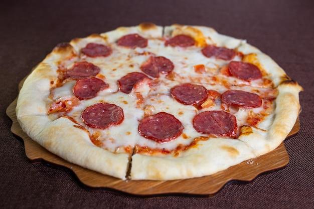Pizza ai peperoni con salsiccia. foto per il menu.