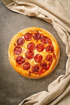 Pizza ai peperoni sul vassoio di legno - stile di cibo italiano
