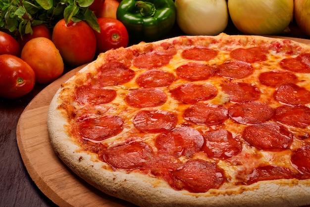Pizza ai peperoni su tavola di legno e verdure in sottofondo
