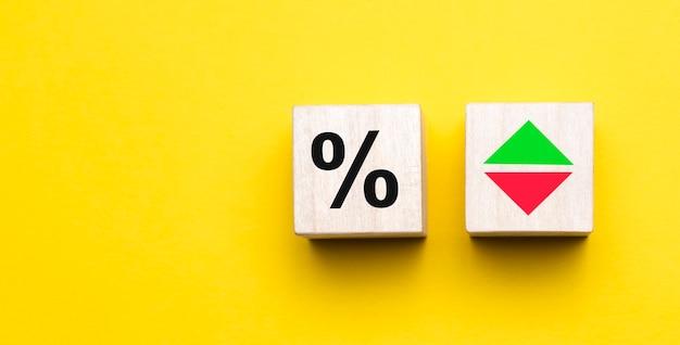 Segno di percentuale su cubi di legno su sfondo giallo con copia spazio. concetto di vendita e sconto.