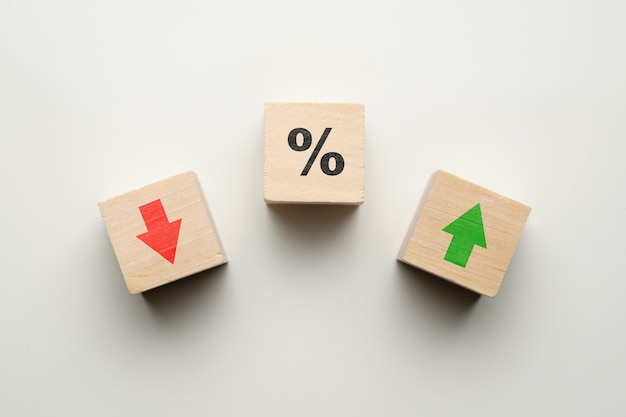 Concetto di percentuale in aumento o in diminuzione della finanza con icone su blocchi di legno.