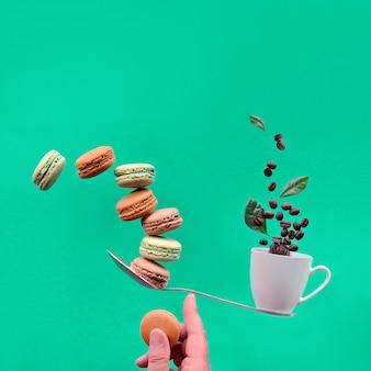 Concetto di perfetto equilibrio. equilibratura tazza di caffè e macaronos sul dito indice. composizione quadrata creativa dell'alimento, copia-spazio sul fondo d'avanguardia del libro verde di biscaglia.