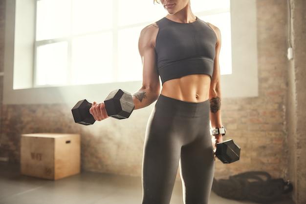 Bicipite perfetto giovane donna atletica con tatuaggio sulla mano in abbigliamento sportivo che si esercita con manubri