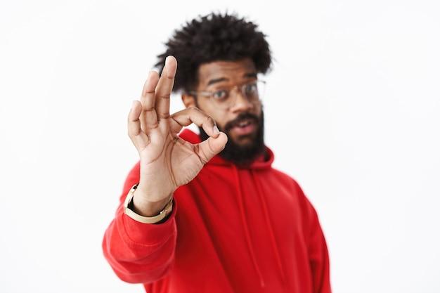 Perfetto. scatto sfocato di ragazzo barbuto afroamericano in felpa con cappuccio rossa tirando la mano a fuoco verso la telecamera che mostra un gesto ok in approvazione e come, felice del risultato eccezionale sul muro grigio