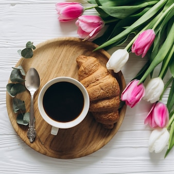 Colazione perfetta per le donne bouquet di tulipani, caffè e croissant.