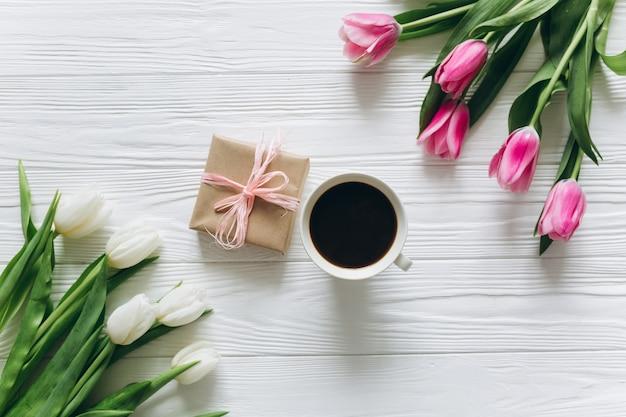 Colazione perfetta per le donne bouquet di tulipani, caffè e regali.