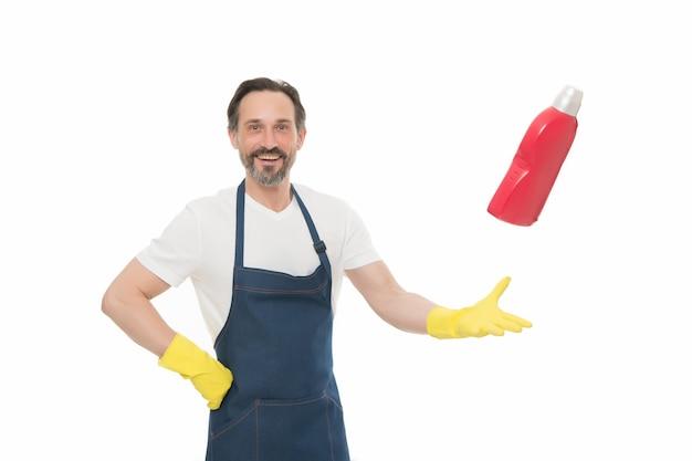 Prodotto detergente perfetto. facile da fare le pulizie. uomo maturo in guanti di gomma. uomo che pulisce casa con detergente. lavare i piatti nel grembiule. protezione della pelle delle mani. routine quotidiana con le faccende domestiche.