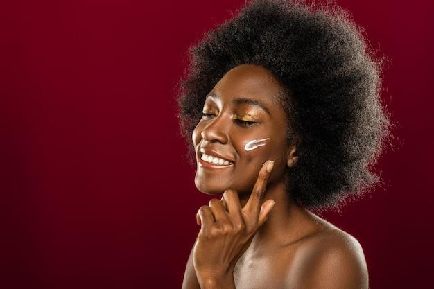 Sensazione perfetta. allegra donna felice chiudendo gli occhi mentre si applica la crema per il viso
