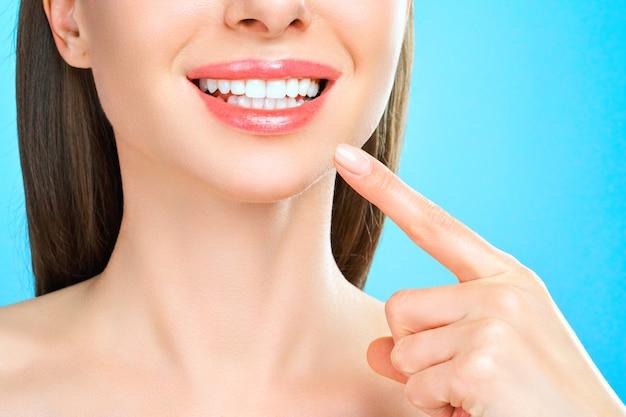 Sorriso perfetto dei denti sani di una giovane donna che sbianca i denti del concetto di stomatologia di cure odontoiatriche