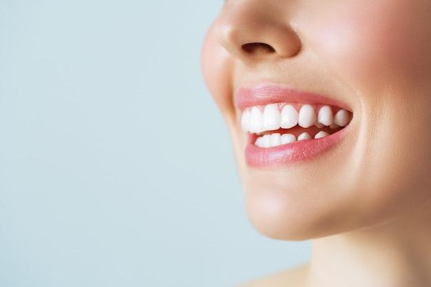 Sorriso di denti sani perfetti di una giovane donna. sbiancamento dei denti. cure odontoiatriche, concetto di stomatologia.