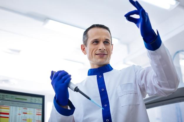 Livello perfetto. operatore medico esperto e attraente che valuta il livello di liquido nella piccola vetreria che tiene la pipetta mentre indossa il camice
