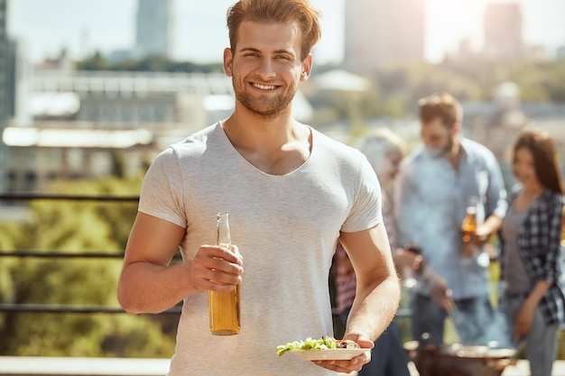 Pranzo perfetto con amici giovane e bell'uomo tiene in mano una bottiglia di birra e un piatto