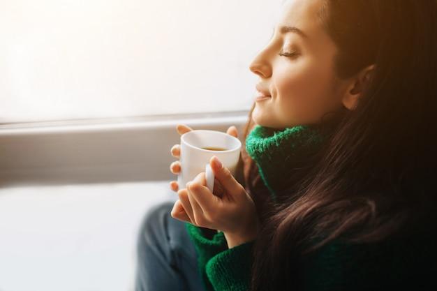 Mattina perfetta una giovane donna bruna si siede su un davanzale e tiene in mano una tazza di tè. modello femminile vestito con un maglione verde si siede vicino e guardando fuori dalla finestra