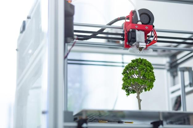 Replica perfetta il primo piano di una stampante 3d in piedi in ufficio e la creazione di un modello colorato