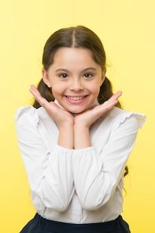 Sorriso perfetto. ragazza felice dimostra il suo sorriso perfetto sfondo giallo. la scolaretta non vede l'ora di tornare a scuola. aspettando settembre. alunno entusiasta del ritorno a scuola.