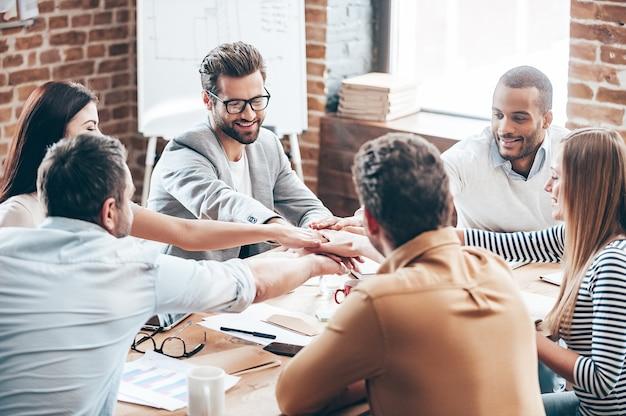 Perfetto lavoro di squadra. un gruppo di sei giovani che si tengono per mano e sorridono seduti alla scrivania dell'ufficio