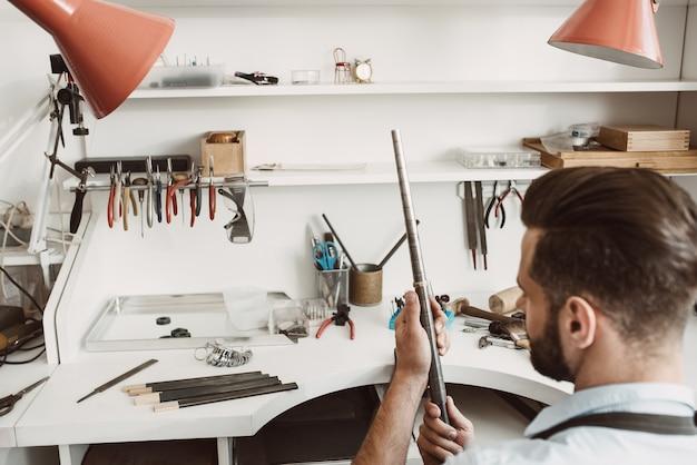 Posto di lavoro perfetto. vista posteriore del giovane gioielliere maschio che controlla la dimensione dell'anello con uno strumento speciale in officina. laboratorio di creazione di gioielli. strumenti da gioielliere
