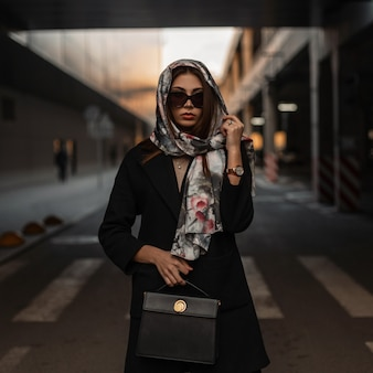 Perfetta giovane donna professionale in eleganti occhiali da sole in cappotto nero alla moda con borsa in pelle con una sciarpa vintage sulla testa in posa sulla strada all'aperto. ragazza europea in città. modello di moda donna sexy.