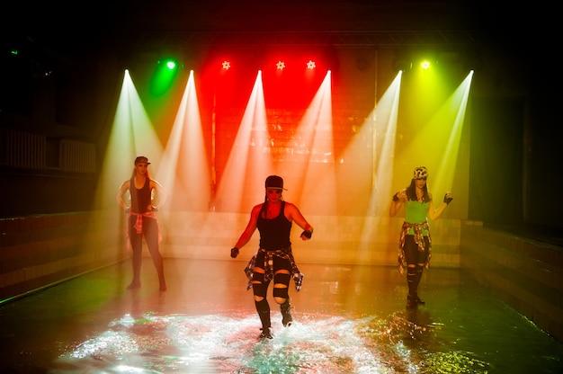 Esibizione sull'acqua di un gruppo di danza sullo sfondo della luce del club.