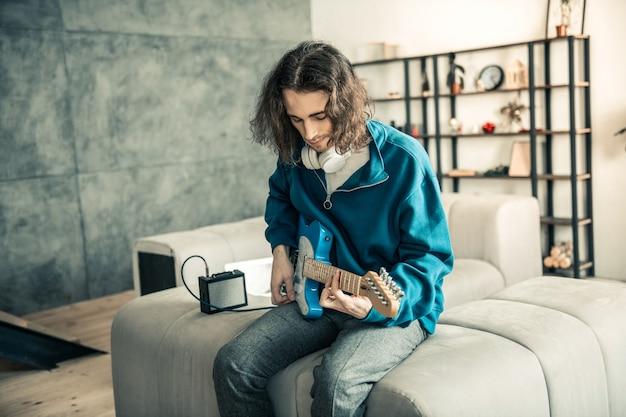 Esecuzione di musica. un bel ragazzo bruno con un taglio di capelli ondulato che si concentra sulla creazione personale mentre suona la chitarra