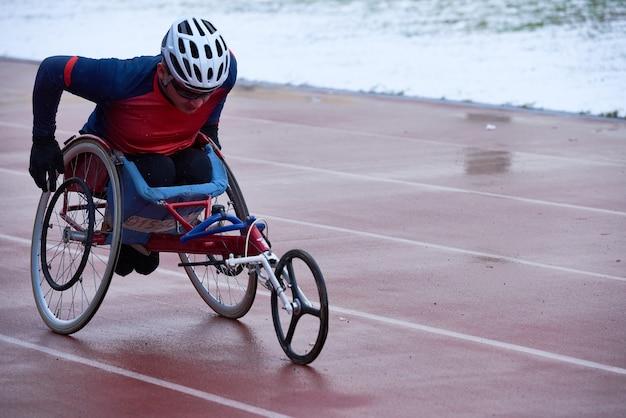 Esecuzione di imprese sportive. atleta maschio volitivo in abbigliamento sportivo e allenamento con il casco in sedia a rotelle da corsa allo stadio di atletica leggera all'aperto