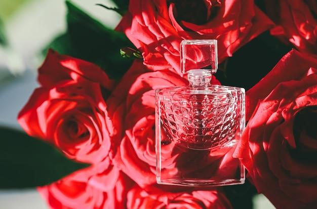 Bottiglie di profumo su bellissimi bouquet di rose in profumeria estiva come regalo di lusso bellezza flatlay backg...