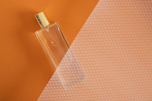 Bottiglia di profumo su sfondo marrone vista dall'alto