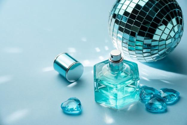 Bottiglia di profumo, sfera da discoteca e cuori di cristallo su una parete blu