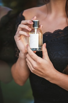 Bottiglia di profumo di una mano femminile. giovane donna alla moda che tiene una bottiglia di profumo. profumo alla moda nelle mani delle donne. ragazza che spruzza profumo. belle mani femminili. profumi per le donne
