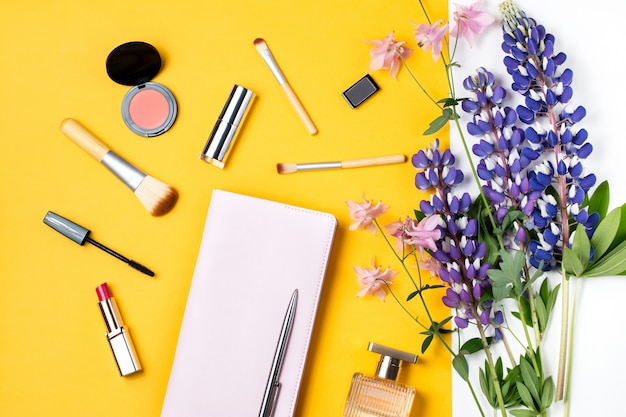 La bottiglia di profumo, i fiori, compone i cosmetici, taccuino su fondo giallo