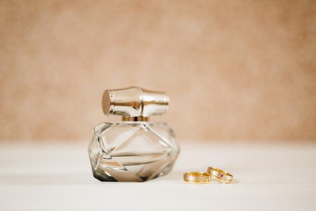 Bottiglia di profumo e fedi nuziali d'oro degli sposi su uno sfondo chiaro light