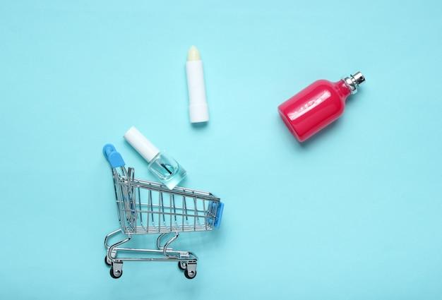 Bottiglia di profumo, rossetto in un carrello su un tavolo pastello rosa blu. minimalismo, concetto di bellezza, accessori