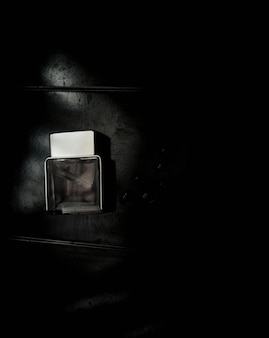 Bottiglia di profumo. mockup su sfondo sgangherato scuro o nero. fragranza per uomo. vista dall'alto.