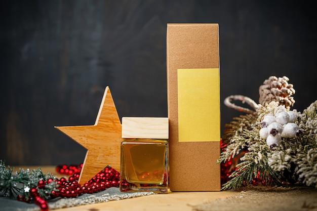 Bottiglia di profumo regalo di capodanno. l'elegante bottiglia di profumo di capodanno è sotto l'albero. profumi alla moda nelle location di capodanno. profumi per le donne