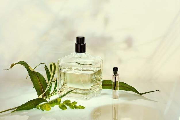 Bottiglia di profumo e campionatore con piante su sfondo naturale verde