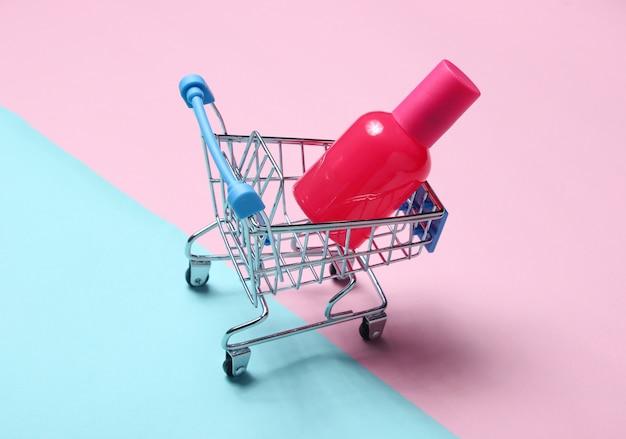 Il profumo imbottiglia un carrello su una tavola pastello rosa blu. minimalismo, concetto di bellezza, accessori