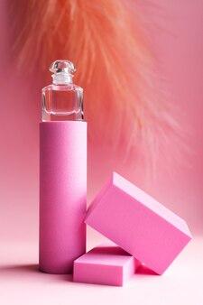 Una bottiglia di profumo si trova su un piedistallo su uno sfondo rosa
