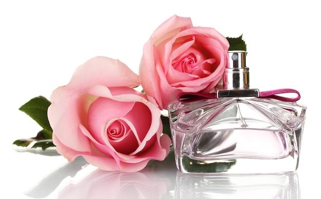 Bottiglia di profumo e due rose rosa isolate su bianco